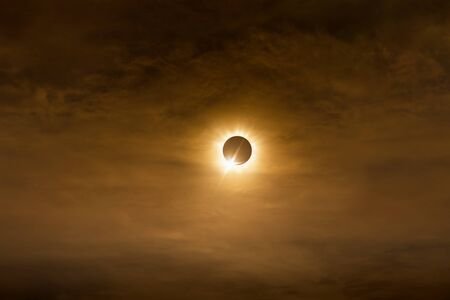 Total solar eclipse in dark red cloudy sky, mysterious natural phenomenon when Moon passes between planet Earth and Sun