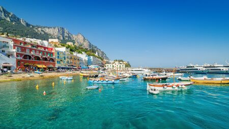 Crowd of tourists walk along seaside promenade, colorful buildings, sightseeing boats, ferryboats with tourists in Marina Grande, Capri Island, Italy.
