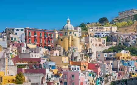 Colorful vibrant housing of Marina Corricella in sunny day in Procida Island, Italy.