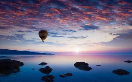 Amazing serene background with lonely hot air balloon flies in glowing sunset sky above calm sea