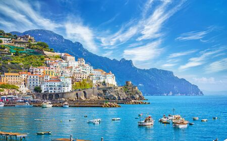Beautiful Amalfi on hills leading down to coast, comfortable beaches and azure sea in Campania, Italy. Amalfi is most popular travel and holyday destination in Europe. Фото со стока