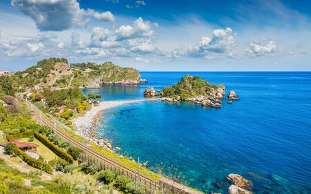 Beautiful Isola Bella, small island near Taormina, Sicily, Italy. Narrow path connects island to mainland Taormina beach surrounded by azure waters of the Ionian Sea.