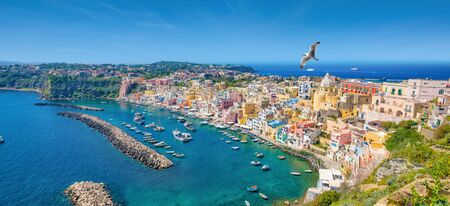 Panoramic view of beautiful Procida in sunny summer day. Colorful houses, cafes and restaurants, fishing boats and yachts in Marina Corricella, clear blue sky and azure sea in Procida Island, Italy. Reklamní fotografie