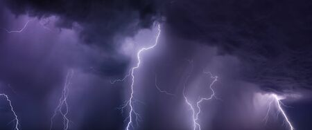 Huge lightnings and heavy rain in dark stormy sky, climate change and weather forecast concept