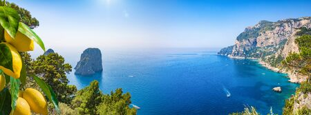 Panoramic collage with famous Faraglioni Rocks, Marina Piccola and Monte Solaro on Capri Island, Italy. Bunches of fresh yellow ripe lemons are in foreground. Reklamní fotografie