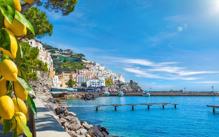 Beautiful seaside town Amalfi in province of Salerno, Campania, Italy. Amalfi coast is popular travel and holyday destination in Europe. Ripe yellow lemons in foreground.
