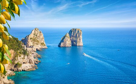 Famous Faraglioni Rocks, Capri Island, Italy. Beautiful paradise landscape with azure sea in summer sunny day and ripe yellow lemons in foreground. Reklamní fotografie