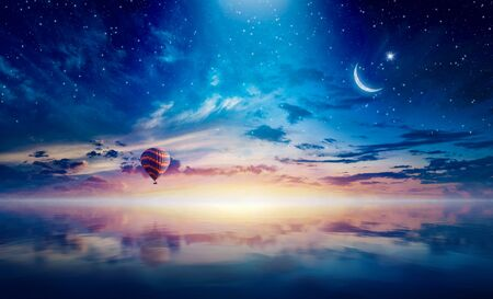 Amazing heavenly background - crescent and hot air balloon rising above serene sea in sunset glowing sky.  Mixed media image.