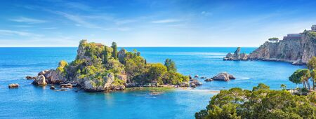 Panoramic view of beautiful Isola Bella, small island near Taormina, Sicily, Italy. Narrow path connects island to mainland Taormina beach surrounded by azure waters of Ionian Sea.