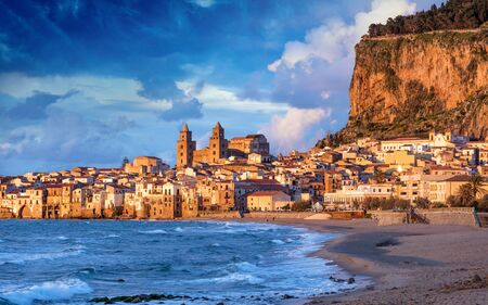Sunset view of long sandy beach and blue sea in Cefalu, town in Italian Metropolitan City of Palermo located on Tyrrhenian coast of Sicily, Italy. Cefalu is popular travel destination in Europe.