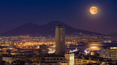 Full moon rises above Mount Vesuvius, Naples and Bay of Naples, Italy. Moonlight reflected in calm sea. Reklamní fotografie