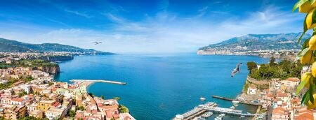 Welcome to Sorrento concept image. Panoramic collage of cliff coastline Sorrento and Gulf of Naples, Italy. Ripe yellow lemons in foreground. Reklamní fotografie