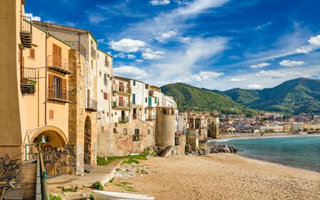 Long sandy beach with fishing boats, blue sea near Cefalu, town in Italian Metropolitan City of Palermo located on Tyrrhenian coast of Sicily, Italy. Cefalu is popular travel destination in Europe.