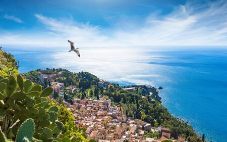 Aerial view of Taormina resort town located in Metropolitan City of Messina, on east coast of Sicily island, Italy. Bright sun in blue sky, azure sea and green tropical plants in summer day.