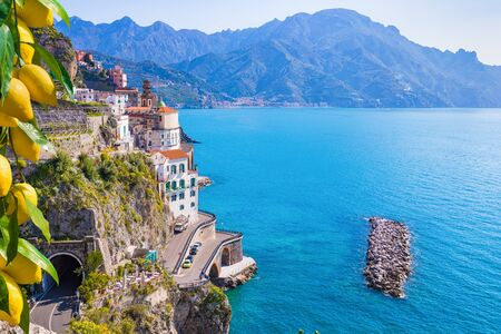 Small town Atrani on Amalfi Coast in province of Salerno, Campania region, Italy. Amalfi coast is popular travel and holyday destination in Italy. Ripe yellow lemons in foreground.