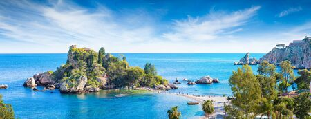 Panoramic view of Isola Bella, small island near Taormina, Sicily, Italy. Narrow path connects island to mainland Taormina beach surrounded by azure waters of Ionian Sea.