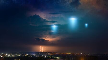 Amazing fantastic background - extraterrestrial aliens spaceship fly above small town, ufo with blue spotlights in dark stormy sky.
