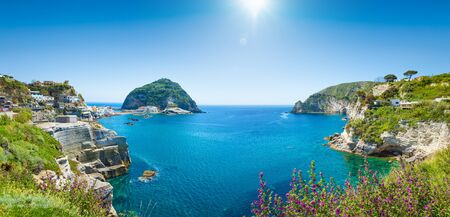 Panoramic collage with green rocky coast and giant rock in azure sea near small village SantAngelo, Ischia Island, Italy.