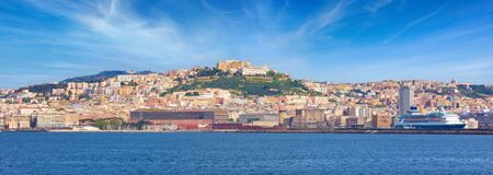 Panoramic view from sea of Naples coastline, Italy. Big cruise ships are in port, cityscape in sunny weather with blue sky and white clouds.