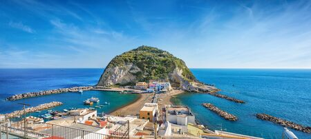 Panoramic view of beautiful coast of village SantAngelo, giant green rock in blue sea near Ischia Island, Italy. Sunny day, blue sky with white clouds and azure sea. Reklamní fotografie