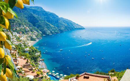 Hermosa Positano con cómodas playas y mar azul claro en la costa de Amalfi en Campania, Italia. La costa de Amalfi es un destino popular de viajes y vacaciones en Europa. Limones amarillos maduros en primer plano. Foto de archivo