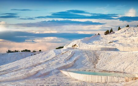 Sunset view of amazing Pamukkale. Travertine terrace formations left by flowing thermal springs in Pamukkale, literally