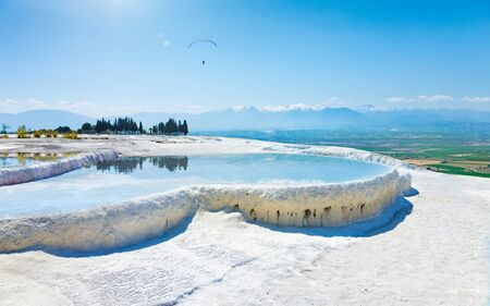 Pool with clear hot water from thermal spring in Pamukkale, Denizli Province in southwestern Turkey. Pamukkale is most visited turkish travel attraction. Lonely paraglider soars in blue sky.