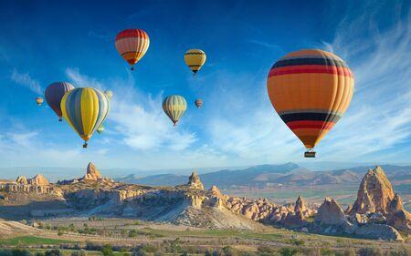 Surise vista di insolito paesaggio roccioso in Cappadocia, Turchia. Mongolfiere colorate volano nel cielo azzurro sopra meravigliose valli con camini delle fate in Cappadocia.
