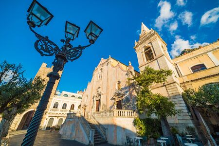 Wide angle view of Square Piazza IX Aprile with San Giuseppe church and Clock Tower in Taormina, Sicily, Italy. Taormina located in Metropolitan City of Messina, on east coast of island of Sicily.