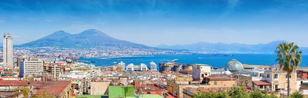 Panoramic view of Naples, Italy. Castel Nuovo and Galleria Umberto I towering over roofs of neighboring houses of Naples and located in foreground. Mount Vesuvius is located on background.