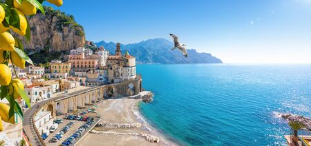 Panoramic view of small town Atrani on Amalfi Coast in province of Salerno, Campania region, Italy. Amalfi coast is popular travel and holyday destination in Italy. Ripe yellow lemons in foreground.
