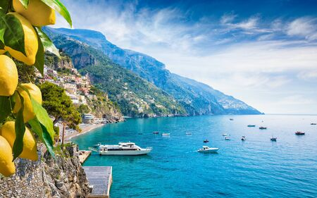 Beautiful Positano with comfortable beaches and blue sea on Amalfi Coast in Campania, Italy. Amalfi coast is popular travel and holyday destination in Europe. Ripe yellow lemons in foreground.