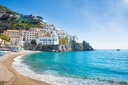 Beautiful Amalfi with hotels on hills leading down to coast, comfortable beaches and azure sea in Campania, Italy. Amalfi coast is popular travel and holiday destination in Europe. 免版税图像
