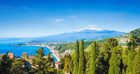 Daylight view of Taormina and beach of Giardini-Naxos located in Metropolitan City of Messina, on east coast of Sicily island, Italy. In background is Mount Etna.