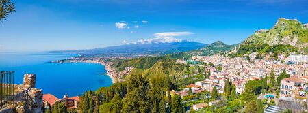 Aerial panoramic view of Taormina located in Metropolitan City of Messina, on east coast of Sicily island, Italy. In background is Mount Etna.