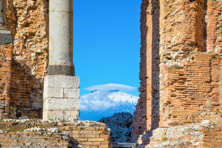 Through ruins of ancient Greek Theater you can see Etna volcano, Sicily, Italy. Foto de archivo