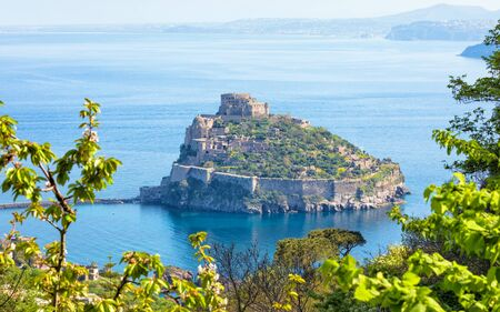 Aerial view of Aragonese Castle, most popular landmark located in Tyrrhenian sea near Ischia island, Italy. Castle stands on volcanic rocky islet that connects to mainland of Ischia by causeway.