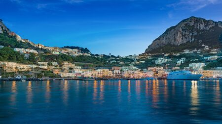 After sunset view of Marina Grande, Capri island, Italy. Illuminated streets of city are reflected in calm sea. Island of Capri is situated 5 km from mainland in Bay of Naples.