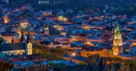 Aerial night view of historical old city district with churches, cathedrals and houses roofs in Lviv, Ukraine. Lviv is one of main cultural centres and largest city and in western Ukraine.