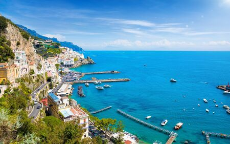 Aerial view of beautiful Amalfi with hotels on hills leading down to coast, comfortable beaches and azure sea in Campania, Italy. Amalfi coast is popular travel and holiday destination in Europe.