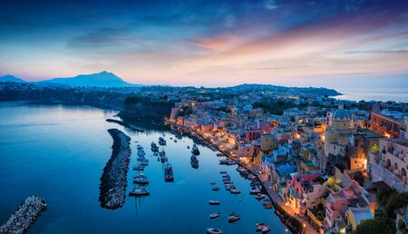 Aerial sunset view of beautiful Procida. Colorful houses, cafes and restaurants, fishing boats and yachts in Marina Corricella, glowing sky and serene sea in Procida Island, Italy. 免版税图像