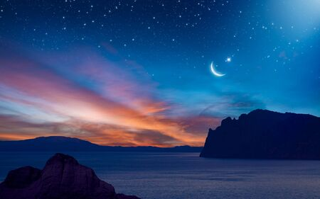 Ramadan background with crescent, stars and glowing clouds with ray from skies above mountains and sea. Month of Ramadan is that in which was revealed Quran. 免版税图像