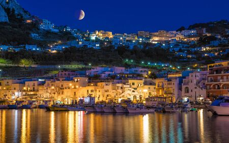 Night view of Marina Grande, Capri island, Italy. Illuminated streets of city are reflected in calm sea. Island of Capri is situated 5 km from mainland in Bay of Naples. 免版税图像