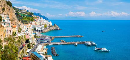 Panoramic view of beautiful Amalfi with hotels on hills leading down to coast, comfortable beaches and azure sea in Campania, Italy. Amalfi coast is popular travel and holiday destination in Europe.