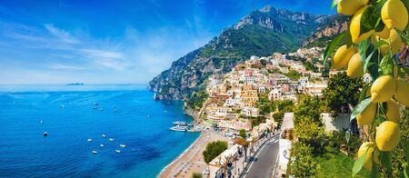 Panoramic view of Positano with comfortable beaches and blue sea on Amalfi Coast in Campania, Italy. Amalfi coast is popular travel and holyday destination in Europe. Ripe yellow lemons in foreground.
