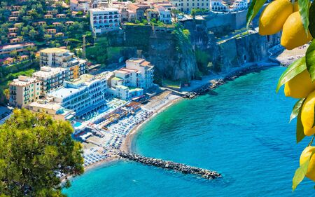 Aerial view of cliff coastline Sorrento and Gulf of Naples, Italy. Clear azure sea and luxury hotels of Sorrento attract lot of tourists from all over world. Ripe yellow lemons in foreground.
