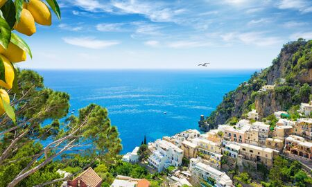 Aerial view of Positano with comfortable beaches and blue sea on Amalfi Coast in Campania, Italy. Amalfi coast is popular travel and holyday destination in Europe. Ripe yellow lemons in foreground.