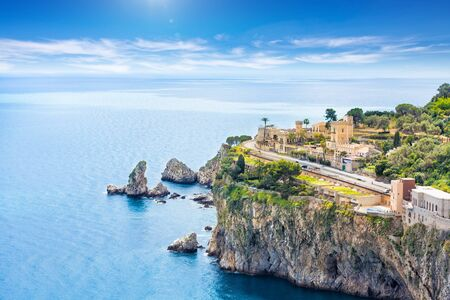 Aerial view of blue sea and rocky coast at Cape Taormina. Taormina located in Metropolitan City of Messina, on east coast of island of Sicily, Italy.