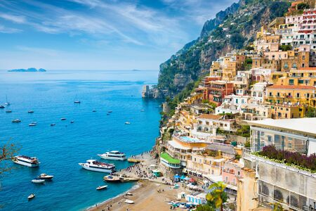 Beautiful Positano with hotels on hills leading down to coast, comfortable beaches and azure sea on Amalfi Coast in Campania, Italy.