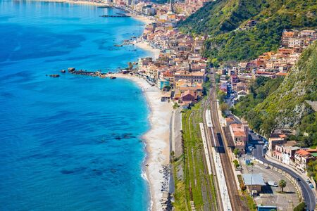 Aerial view of Taormina-Giardini station and Giardini Naxos, comune in Messina on Sicily Island, Italy. It is situated on coast of Ionian Sea between Cape Taormina and Cape Schiso.